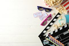 Flat lay. 3d glasses, buckets with popcorn, tickets, clapperboard, drink, on white wood
