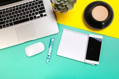 Flat lay design of work desk with labtop notebook, smartphone and cactus on green and yellow background stock images