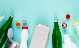 Flat lay of different wastes ready for recycling on green background. Plastic, glass, paper, tin cans. stock photo