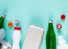 Flat lay of different wastes wastes ready for recycling on green background. Plastic, glass, paper, tin cans. stock photo