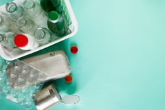 Flat lay of different wastes wastes ready for recycling on green background. Plastic, glass, paper, tin cans. stock image