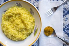 Saffron rice with a spoon of its principal ingredient. Flat lay of a dish of saffron rice with a spoon of the principal ingredient Stock Photos