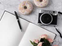 Flat lay with donuts, flowers, camera and notepad on white marble background. Summer concept stock photography