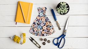 Dress made of buttons and tailoring items. Flat lay with dress made of buttons, notebook, pencil and tailoring items on wooden surface royalty free stock photos