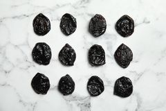 Flat lay of dried plums on marble background royalty free stock photography