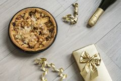 Homemade apple pie, with golden present and bottle of champagne royalty free stock photos