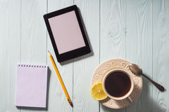 Flat lay of e-book reader, pencil and notebook on table. Stock Image