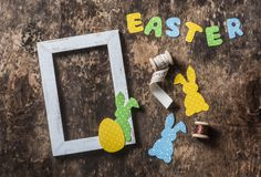 Flat lay Easter background. Empty frame, paper homemade rabbits, ribbon, paper letters on wooden rustic background, overhead view. Easter decorations Stock Images