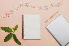 Flat lay empty book and pencil, tablet for design work. With clipper and small cactus on yellow pastel color background Royalty Free Stock Photos