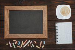 Flat lay with empty chalkboard, cup of coffee, blank notebook and chalks on dark. Wooden tabletop Stock Photos