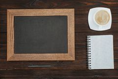 Flat lay with empty chalkboard, cup of coffee, blank notebook and pen on dark. Wooden tabletop Stock Photo
