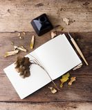 Flat lay empty notebook with autumn leaves on old wooden table. Art mock up