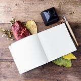 Flat lay empty notebook with autumn leaves on old wooden table. Art mock up. Text space Royalty Free Stock Photo