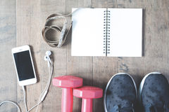 Flat lay of empty notebook, cellphone and sport equipment on woo Royalty Free Stock Photo