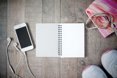 Flat lay of empty notebook, cellphone and sport equipment on woo Stock Images
