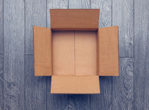 Flat lay of empty open box on wooden surface Royalty Free Stock Images