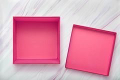 Flat lay of empty pink gift box with lid on natural marble texture. Pink cardboard box with cove. R. Top view royalty free stock photos