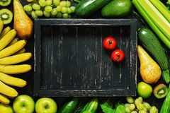 Flat lay empty wooden black tray and frame of fresh vegetables and fruits. Top view, copy space.  royalty free stock images