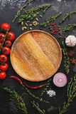 Flat lay empty wooden plate and frame of vegetables, herbs and spices. Top view, copy space. Different seasoning.  royalty free stock photo
