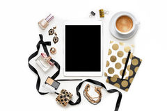 Flat lay fashion feminine home office workspace with tablet, cup of coffee, stylish black gold notebooks, cosmetics and jewelry on. White background. Women`s Royalty Free Stock Photo