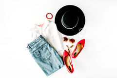 Flat lay feminine clothes and accessories collage with blouse, jeans, sunglasses, bracelet, lipstick, red high heel shoes, earring. S and hat on white background royalty free stock image