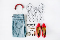 Flat lay feminine clothes and accessories collage with shirt, jeans, glasses, mascara, lipstick, red high heel shoes, earrings and Stock Image