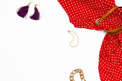 Flat lay feminine clothes and accessories on white background. Red dress, earrings, pearl bracelet. Top view Stock Images