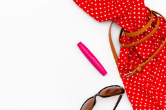Flat lay feminine red dress and accessories: sunglasses and mascara on white background. Royalty Free Stock Images