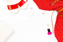 Flat lay feminine red dress, shoes, pearl bracelet, handbag, nail Polish and earrings on white background. Royalty Free Stock Photography