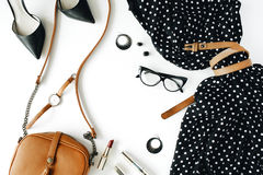 Flat lay feminini clothes and accessories collage with black dress, glasses, high heel shoes, purse, watch, mascara, lipstick, ear Royalty Free Stock Images