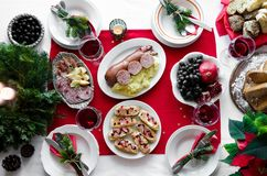 Flat-lay of festive table setting for holiday dinner with dishes. Traditional Italian Christmas dinner - potatoes with Cotechino, royalty free stock photography
