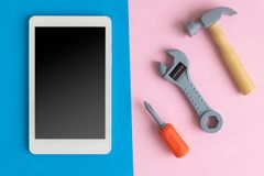 Flat lay of fixing mobile device abstract with plastic tools. Digital tablet device or mobile phone with hammer, wrench and screwdriver on pastel background stock images
