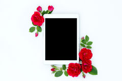 Flat lay floral frame with tablet, red and beige rose flower buds on white background. Stock Images