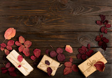 Flat lay frame of autumn crimson leaves and gift boxes on a dark Stock Image