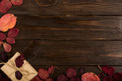 Flat lay frame of autumn crimson leaves and gift boxes on a dark Stock Photo