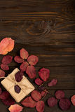 Flat lay frame of autumn crimson leaves and gift boxes on a dark Royalty Free Stock Image