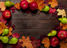 Flat lay frame of autumn crimson and yellow leaves, pears and ap Stock Images