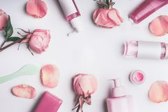 Flat lay frame of flowers and cosmetics products with Rose essential oil. Flat lay frame of flowers and cosmetics products with Rose essential oil: toner,serum royalty free stock images