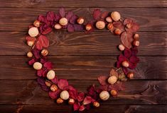 Flat lay frame in the form of a heart of autumn crimson leaves, Stock Photo
