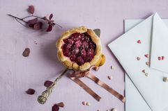 Flat lay french charlotte with raspberry on spoon and white envelop. Greeting card Royalty Free Stock Photo