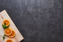 Fresh citrus fruits, half cut orange slices on cutting board, dark stone background, flat lay royalty free stock photography