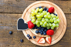 Flat lay, fresh fruits with a heart slate on wooden table, copys Royalty Free Stock Photography