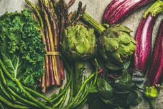 Flat-lay of fresh green and purple vegetables, clean eating. Flat-lay of green and purple vegetables over grey concrete background, top view. Local seasonal Stock Photos