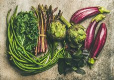 Flat-lay of fresh green and purple vegetables over concrete background. Flat-lay veriety of green and purple vegetables over grey concrete background, top view Stock Image