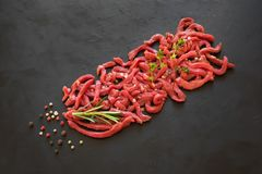 Flat-lay of fresh raw beef meat on black table. royalty free stock image
