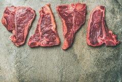 Porterhouse, t-bone and rib-eye steaks over grey concrete background Stock Images