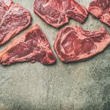 Porterhouse, t-bone and rib-eye steaks over grey background, square crop. Flat-lay of fresh raw beef meat steak cuts over grey concrete background, top view Stock Images