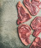 Porterhouse, t-bone and rib-eye steaks over grey background, copy space. Flat-lay of fresh raw beef meat steak cuts over grey concrete background, top view, copy Royalty Free Stock Photography