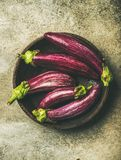 Flat-lay of fresh raw Fall harvest purple eggplants or aubergines. In wooden bowl over concrete stone background, top view. Healthy Autumn vegan cooking Royalty Free Stock Photos