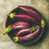 Flat-lay of fresh raw Fall harvest purple eggplants, square crop. Flat-lay of fresh raw Fall harvest purple eggplants or aubergines in wooden bowl over concrete Stock Photo